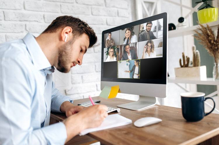 Man taking notes during video conference call